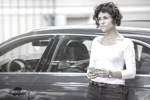 Woman leaning on her car, using her smartphone