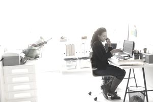 Woman in an office pays with a credit card while seated at a computer