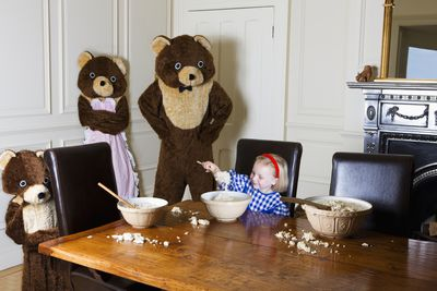 A little girl eating from a bowl at a table surrounded by three bears