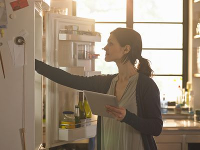 A homeowner checks her fridge after a storm-induced power outage.