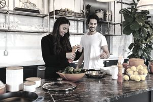 A couple cooking in a new home they bought with mortgage down payment gifts.