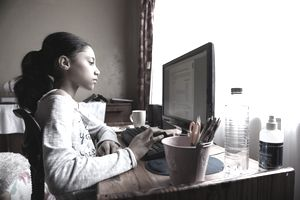 Young girl doing schoolwork at home on a desktop computer during pandemic school closures.