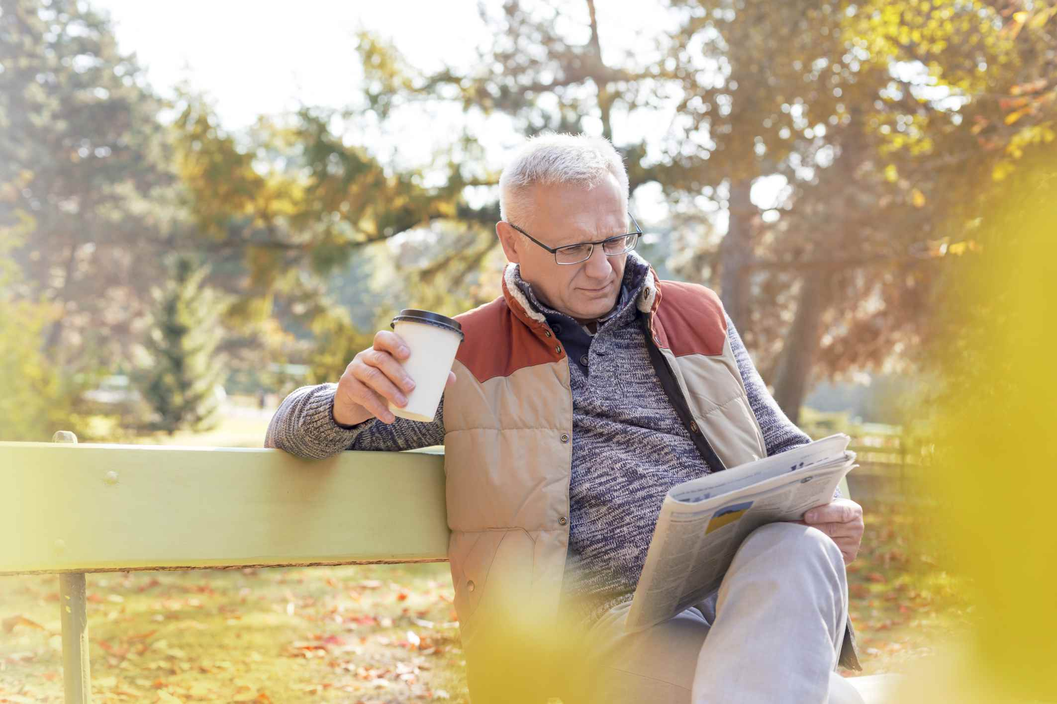 Older man reading paper with coffee on a park bench