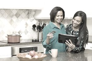Mother and daughter buy something together in kitchen from an tablet while the mother holds a credit card.