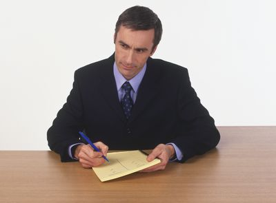 a businessman making a list of pros and cons