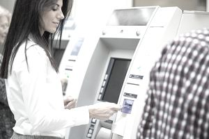 Close-up of female hand inserting credit card in ATM machine