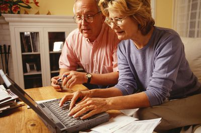 elderly couple working on finances with computer
