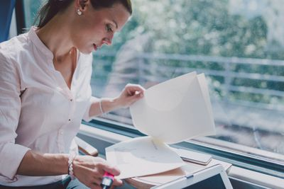A person looks at paperwork near a window.