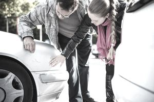Close-up of man and younger woman examining car after accident.