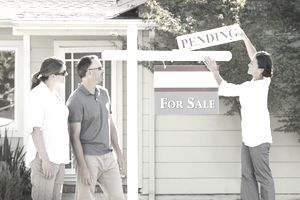 """Realtor hanging a """"Pending"""" sign on a home for sale, with homeowners watching"""