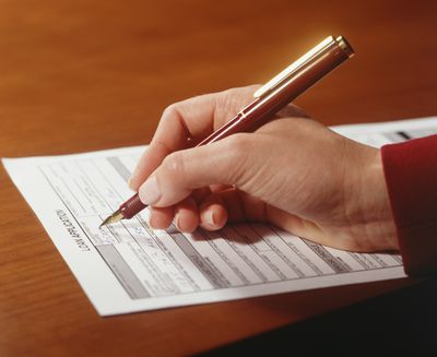 a hand signing an amortized loan document