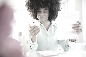 A young woman holding a document and checking her phone