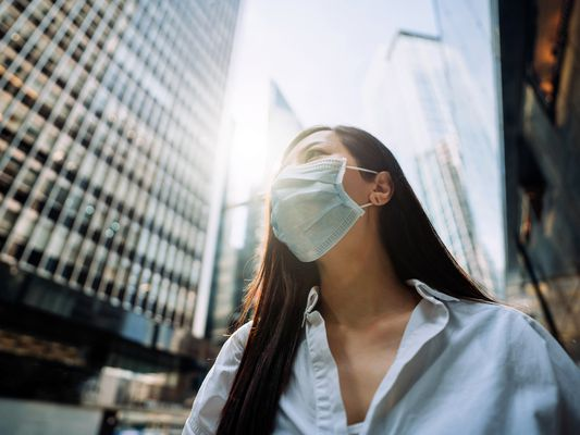 Young Asian businesswoman wearing face mask stands on a downtown city street against corporate skyscrapers.