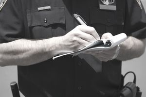 Police officer writing a ticket for a high risk driver