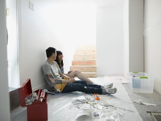 Couple working on home maintenance projects taking a break and sitting on the floor