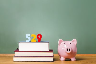 the numbers 529 sit on top of three textbooks laying on a table next to a piggy bnak