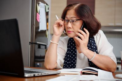 Mature woman on phone looks at laptop in kitchen