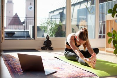 person doing yoga at home in front of her laptop