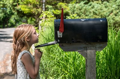 Girl looking inside a rural mailbox outdoors