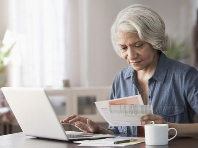 Older woman at a desk entering information from statements into a laptop