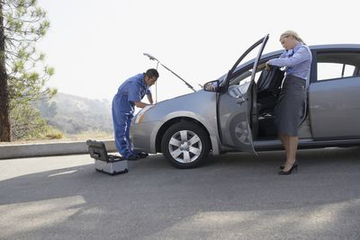 Woman standing next to car while a car technician works under the hood