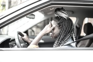 Black woman with braids is driving. She looks stressed, with a hand on her forehead.