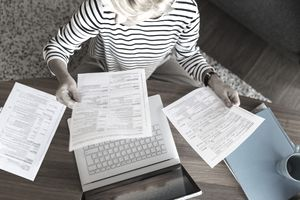 Woman with documents using laptop at home
