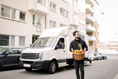 Young delivery driver carries wicker fruit basket in front of van