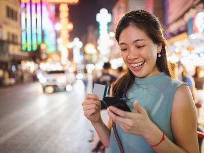 Asian Millennial women using crypto wallet paying and Mobile banking investment using mobile and credit card with happy emotion