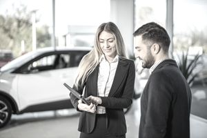 Car saleswoman showing to male customer car performance on tablet