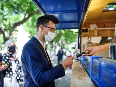 Portrait of young businessman with face mask buying coffee outdoors in city.