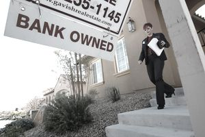 "Realtor exiting out of a home for sale with ""Bank Owned"" signage in yard"