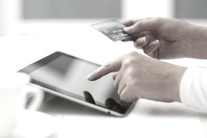 A person entering their credit card number into a tablet.