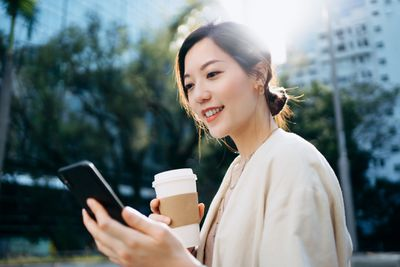 A young businesswoman checks her smartphone while drinking coffee from a to-go cup.