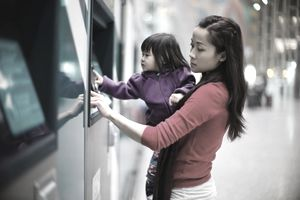 Young mom & baby using an automatic teller machine in a train station.