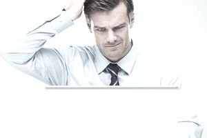 Man sitting in front of a laptop and scratching his head while trying to find a file