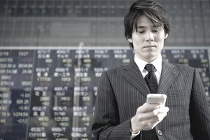 A businessman in front of a stock ticker