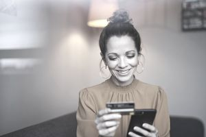 Smiling woman using smartphone and credit card at home