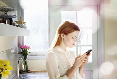 Woman texting on mobile in kitchen