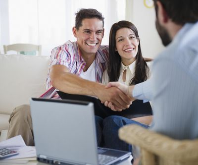 Couple greeting a real estate agent in front of a laptop on a coffee table