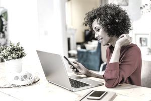 Smiling young woman works on laptop at dining room table