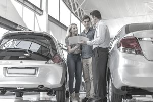 Young Couple Standing Between Two Cars in Showroom With Car Salesman Holding an Auto Manual
