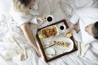 In this overhead photograph a man and a woman dressed in robes sit atop a hotel bed and enjoy a continental breakfast of pastries, coffee, and fruit juice.