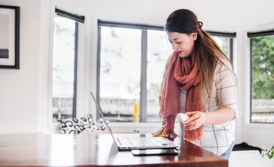 Woman cleaning table while working on laptop