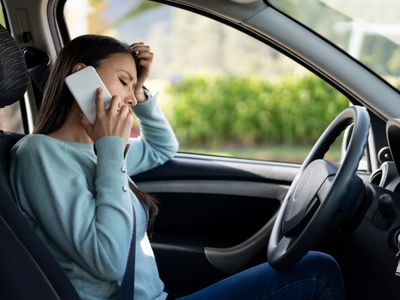 Woman in driver's seat making call to her insurance company