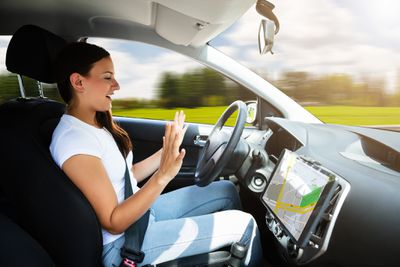 Side view of woman sitting in self-driving car