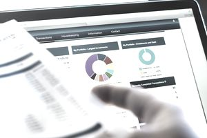 Investor checking performance of financial portfolio online and reviewing investment statement.