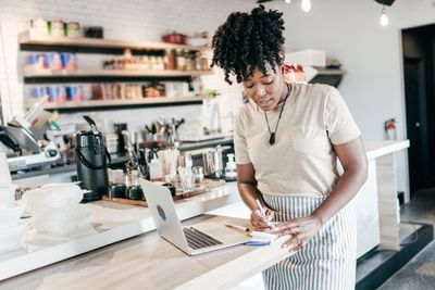 Coffee shop owner doing paperwork with laptop