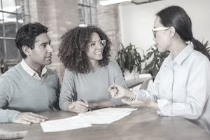 A young couple signs up for a credit builder loan at the local bank branch.
