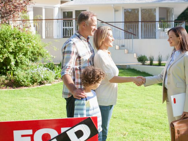 Realtor congratulating family outside a house with a